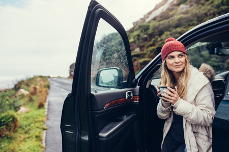 Beautiful female standing by the car with coffee. Smiling woman holding coffee and looking away. Archivio Fotografico