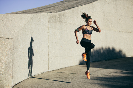 Fitness woman doing cardio interval training outdoors. Caucasian female in sportswear exercising outdoors in morning.