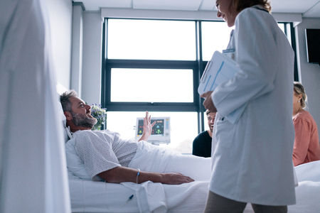 Female doctor visiting patient in hospital room. Sick man lying in bed with family sitting by and doctor. Stock Photo