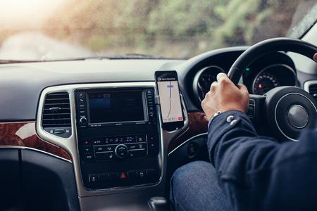 男は、モバイルナビゲーションシステムと車を運転します。車の中で地図 gps ナビゲーションと携帯電話を使用して男性。