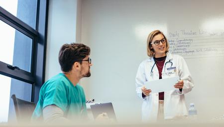 Female doctor leading meeting in hospital. Medicine professional briefing her team in boardroom.