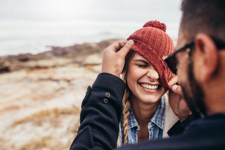Ciérrese encima del retrato de la pareja joven sonriente que se divierte al aire libre. Hombre y mujer disfrutando en un día de invierno en la playa.