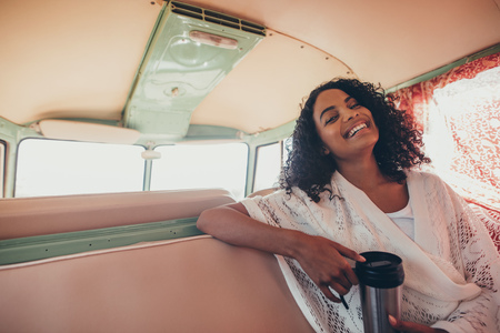 Young woman sitting in backseat of van with coffee and smiling. African woman enjoying on road trip. Stock Photo
