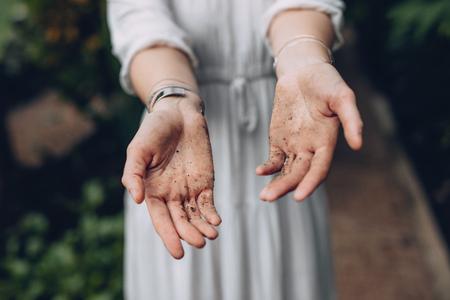 Gros plan d'une femme travaillant dans la jardinerie. Femme jardinier montrant ses mains couvertes de terre. Banque d'images - 93550546