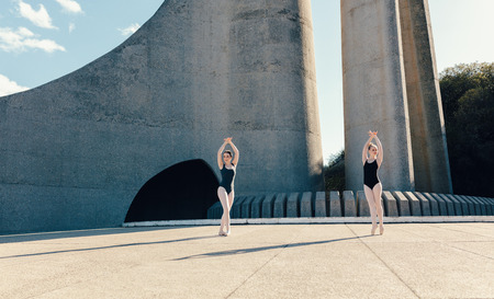 Ballet dancers practicing dance moves outdoors. Ballet dancers performing a duet in synchronization.