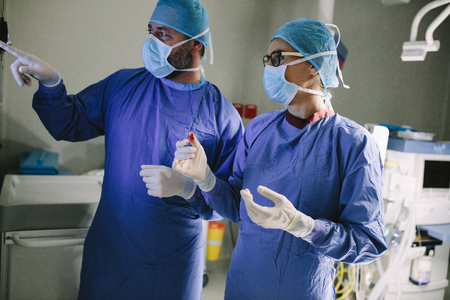 Surgeon looking at medical monitor during surgery. Doctor checking monitor for patient health status. Stock Photo