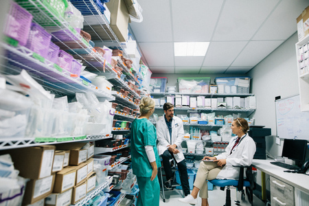 Medical staff discussing in hospital pharmacy. Doctors and nurse talking in hospital pharmacy. Archivio Fotografico