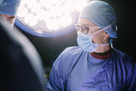 그녀의 팀 병원 수술실에서 수술을 수행하는 집중된 외과. 운영 극장에서 수술하는 동안 의료진입니다. 스톡 콘텐츠
