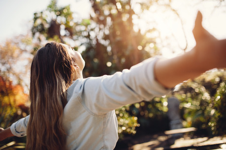 Young woman spreading hands with joy and inspiration outdoors. Female feeling free with arms wide open. Stock Photo