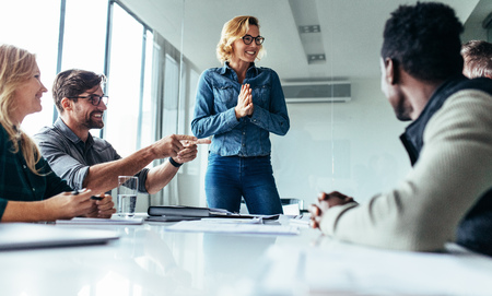 Young happy woman presenting her idea to colleagues in meeting. Businesspeople discussing about new project. Stock Photo