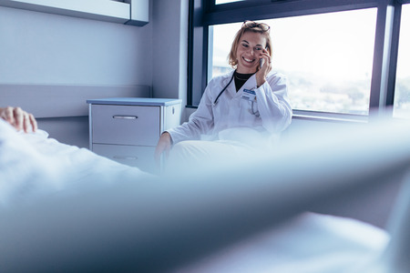 Happy female doctor sitting in hospital room and making a phone call. Medical professional in hospital ward using mobile phone. Stock Photo
