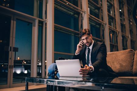 랩톱에서 작업 하 고 공항 터미널에서 핸드폰에 얘기하는 젊은 사업가. 공항 라운지에서 그의 비행을 기다리는 백인 사업가.