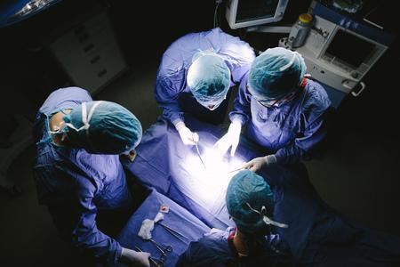 수술 용 극장에서 수술을 수행하는 외과 의사의 팀의 상위 뷰 쐈 어. 병원 운영 극장에서 의사의 그룹입니다.