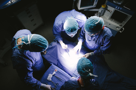 Top view shot of team of surgeons performing surgery in operation theater. Group of doctors in hospital operating theatre. Stock Photo