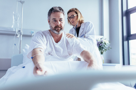 Doctor examining mature man in hospital bed. Patient sitting in bed with female doctor checking his heartbeats. Stock Photo