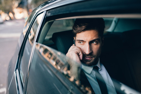 Handsome businessman talking on the mobile phone while sitting on back seat of a car. Caucasian male business executive travelling by a car and making phone call.