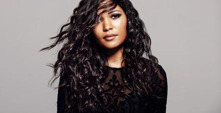 긴 곱슬 머리와 매력적인 갈색 머리입니다. 회색 배경에 물결 모양 헤어 스타일 여성 패션 모델입니다.