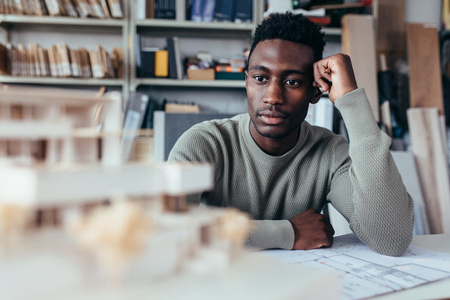new: Young african architect looking at architecture house model and thinking about new ideas. Male designer sitting in office and working on new project.