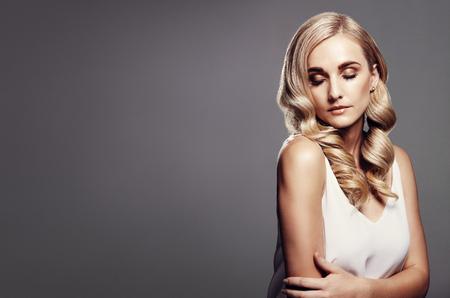 긴 금발 머리를 가진 아름 다운 여자입니다. 복사 공간이 회색 배경 물결 모양 헤어 스타일 금발 모델. 스톡 콘텐츠