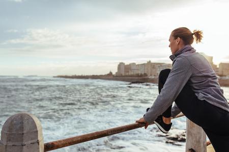 Estilo de vida saudável. Mulher no sportswear que estica seus pés em trilhos no passeio do beira-mar. Foto de archivo - 86047866
