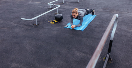Fitness woman doing push-ups at outdoor gym. Young and fit sport model training in gym outdoors. Stock fotó