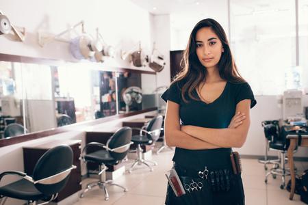 彼女のサロンに折り畳まれた手で立っている女性。すべての理髪アクセサリーとプロの美容師は、彼女の腰に関連付けられます。