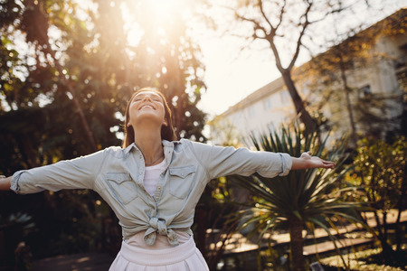 Happy young woman with arms wide open in nature breathing outdoors. Caucasian female enjoying fresh air in the park.