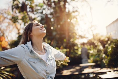 Young female model standing outside with her arms wide open. Woman at park enjoying fresh air. Imagens