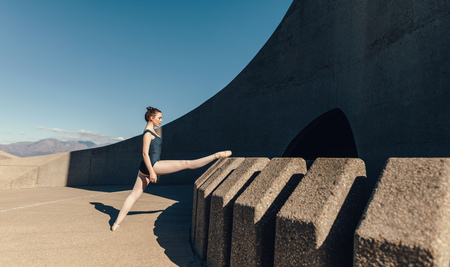 Ballet dancer warming up before dance practice. Ballet dancer stretching her legs placing in on an elevated structure.