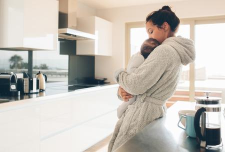 バスローブ姿で彼女の腕の中で赤ん坊を保持の母。朝のキッチンで彼女の息子を持つ女性。