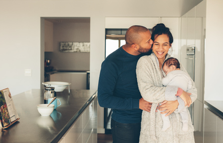 Man kissing his wife holding a newborn baby boy in kitchen. Lovely young family of three in morning in kitchen. Stock Photo