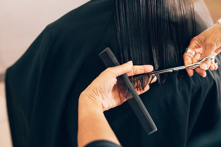 Close up of hair stylist cutting the hair to a straight level. Hairdresser using comb and scissors for a hair cut. Stock Photo