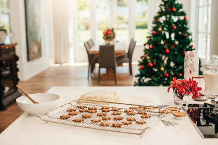 Tray of baked star cookies and dough placed on kitchen table. Decorated Christmas tree in the background. 版權商用圖片 - 86275840