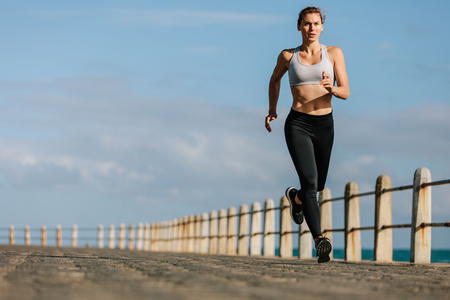 Fit sportswoman running on a road by the sea. Female runner training on a seaside promenade.