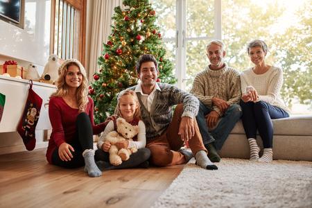 Portrait der Multi-Generation-Familie vor Weihnachtsbaum . Glückliche Familie , die zu Hause während des Weihnachten sitzt