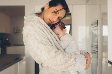 젊은여자가 그녀의 신생아 아기를 들고. 귀여운 어린 소년 부엌에서 그의 어머니의 팔에서 자 고. 스톡 콘텐츠 - 86481778