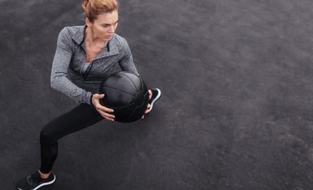 Eignungsfrau, die an der Freiengymnastik unter Verwendung des Medizinballs ausarbeitet. Sportlerin, die draußen mit Medizinball ausdehnt. Exemplar für Text. Standard-Bild
