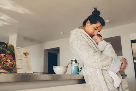 Loving mother carrying her newborn baby boy and standing in kitchen. Woman in bathrobe holding her sleeping son. Banque d'images
