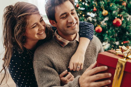 christmas spending: Couple with gift box sitting near Christmas tree. Smiling woman holding her partner from behind while spending happy moments celebrating Christmas.