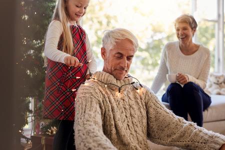 背景に座って祖母と彼女の祖父の首の周りにクリスマスライトを置く小さな女の子。クリスマスの間に家を飾りながら楽しんでいる家族。