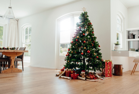 Interior of living room decorated for Christmas. Decorated Christmas tree with gifts all around it. Standard-Bild