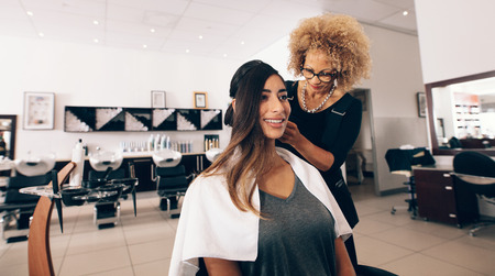 Woman hairdresser at work in salon. Young woman getting a stylish hairdo done at salon.