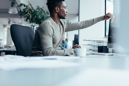 Young african man putting post-it note on computer monitor. Black male working at his desk in office.