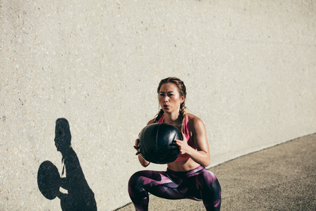 Sportswoman doing squat exercises with fitness ball. Female exercising and stretching with medicine ball outdoors.