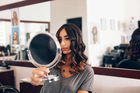 Young woman looking at a handheld mirror after the hairdo. Woman holding a small round mirror at beauty salon. Zdjęcie Seryjne - 89397151