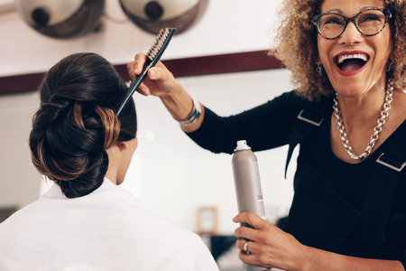 Senior woman hairdresser holding a hair setting spray and a brush at salon. Hair stylist in a happy mood while at work in salon.