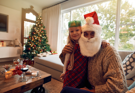 Beautiful little girl with santa claus at home looking at camera. Girl wearing crown and grandfather in santa costume on a christmas eve.