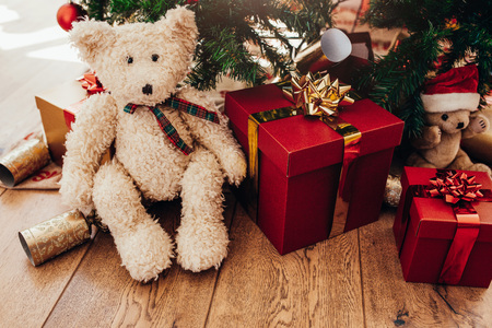 Close-up of a teddy bear and gifts placed under Christmas tree. Decorated gift boxes and  Christmas crackers for Christmas celebrations. Stock Photo