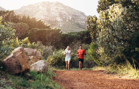 Man and woman jogging on a muddy park trail. Morning jogging couple running together.