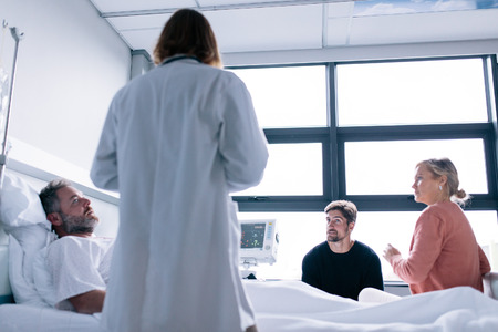Female physician visiting patient in hospital room. Male patient lying in hospital bed with his friends and doctor. Stock Photo